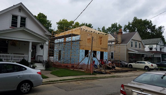 Wood frame house under construction in a lower-middle-class neighborhood