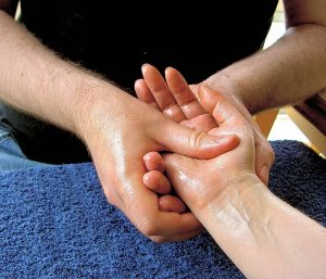 Photograph of a man massaging a woman's hand with her palm facing upwards, using baby oil as a lubricant.