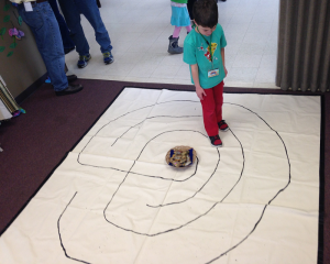Boy waling on a labyrinth drawn on paper on the floor