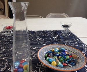 Colorful, polished stones in a decorative dish, next to a tall glass vase holding a few stones
