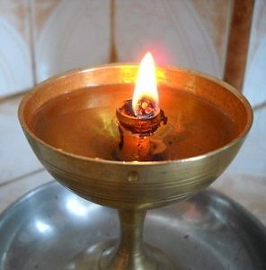 A metal chalice containing oil, a wick, and a flame