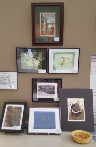 Nine pieces of framed artwork on the wall and counter in Heritage UU Church's Great Hall.
