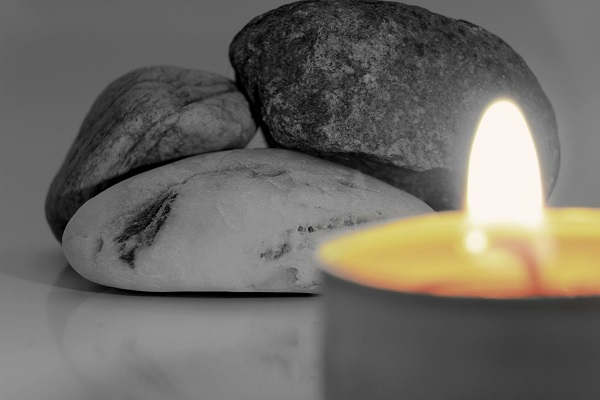One lit candle with three stones in the background.