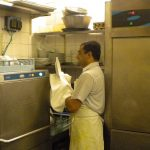 Man operating a large dishwashing machine in a restaurant.