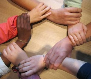 The hands of seven people, each holding the wrist of another person, forming a circle.