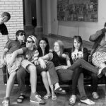 A group of eight teens of mixed genders, mostly Caucasian, crammed on and near a sofa in a museum.