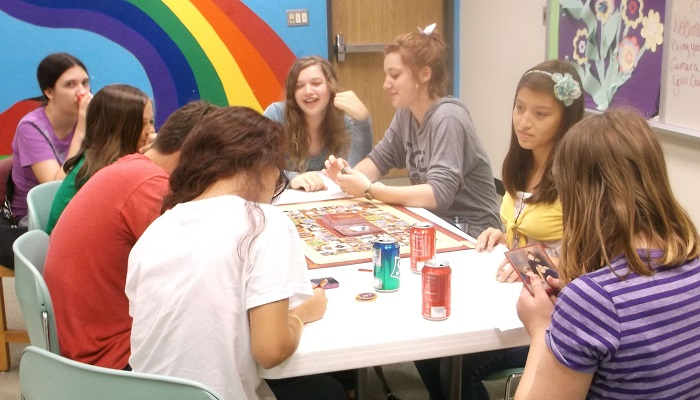 Eight teen-agers sit around a table playing a board game.