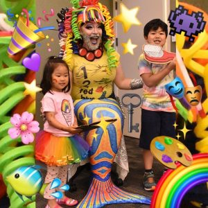 Colorful picture of person dressed as a cartoon clownfish with a big smile, with two children standing nearby and with many picturs and symbols added to the picture.
