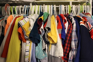 Many children's shirts on hangers in a crowded closet.