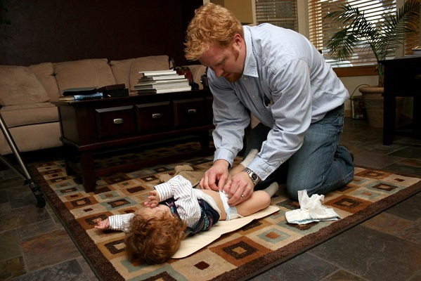 Young businessman kneeling on a run on an office floor, chaning a child's diaper