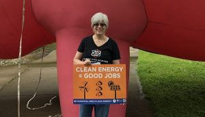 "A member of Heritage UU Church stands with a sign that says ""Clean Energy = Good Jobs,"" at the rally against Ohio bill HB6."