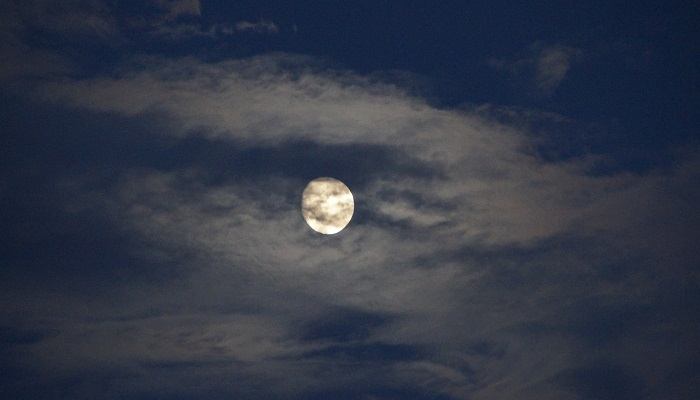 A nearly-full moon, partially covered by whispy clouds